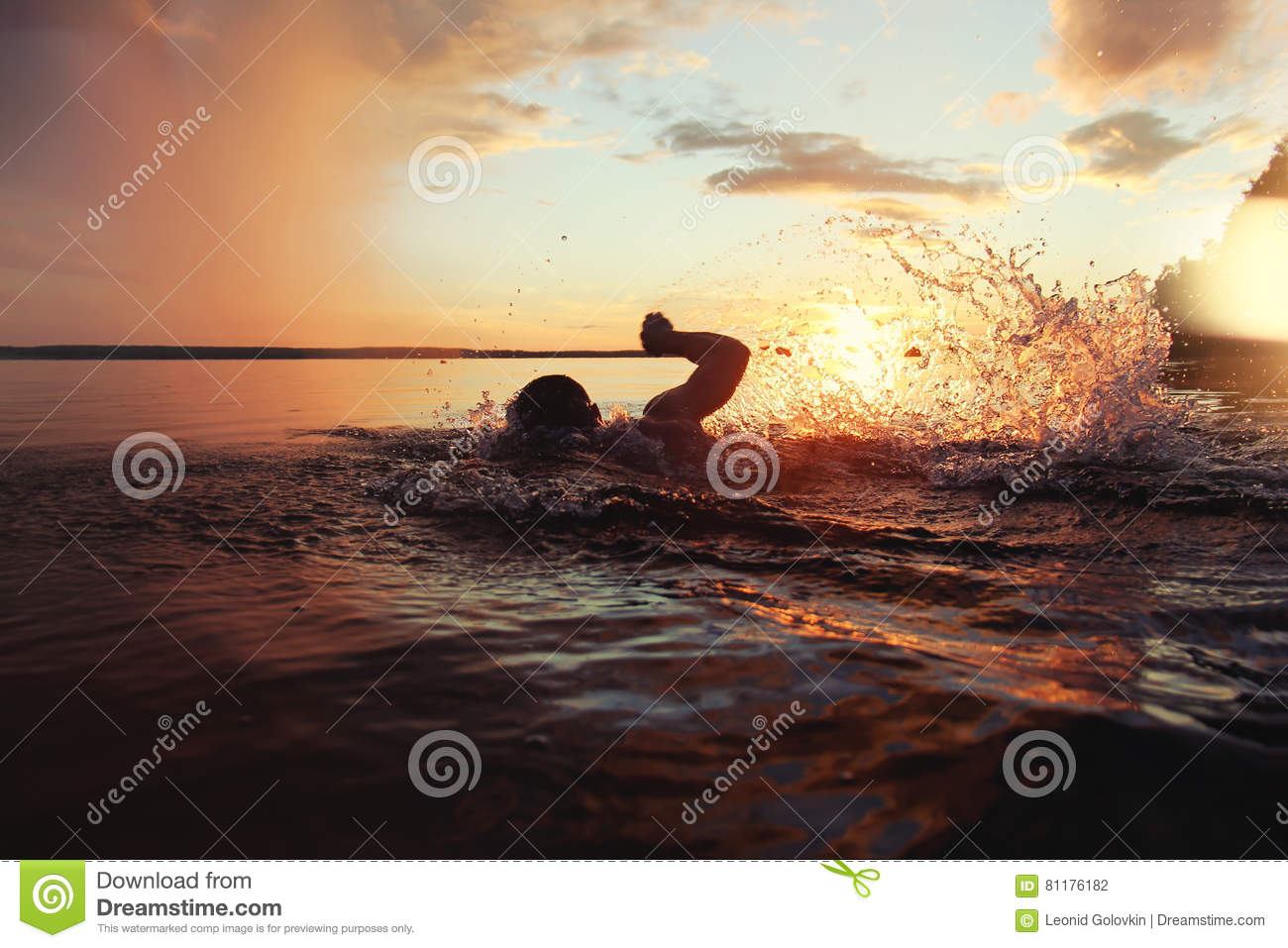 Athletic man is trained to swim in a lake at sunset. It flies a lot of water splashing