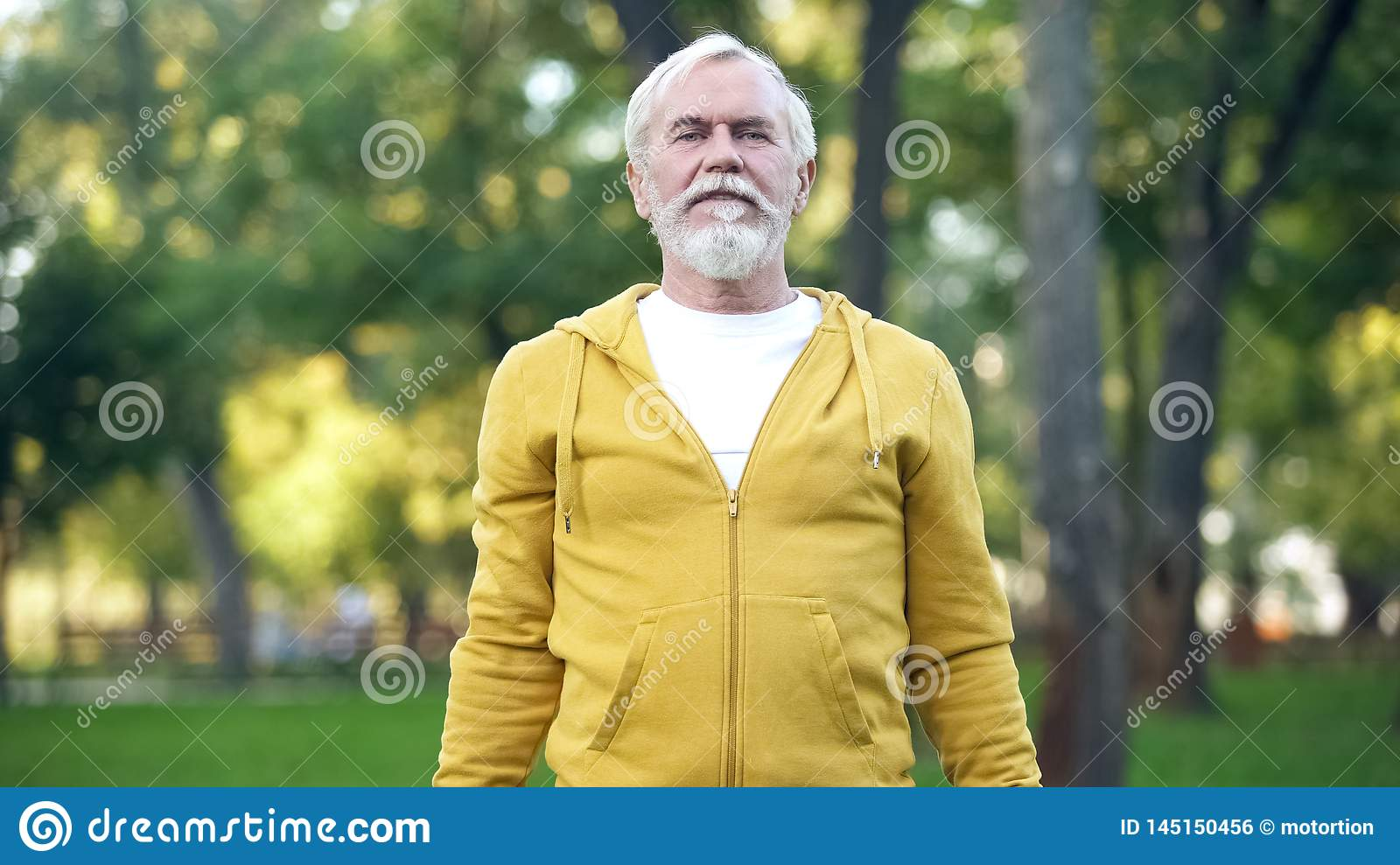 Athletic mature man doing morning exercises in park, healthy lifestyle, aging