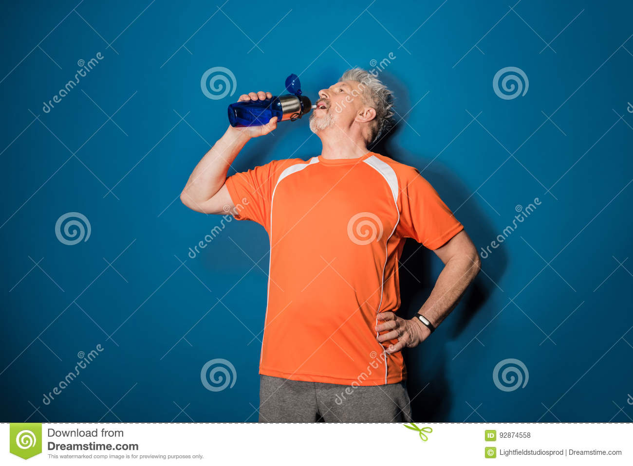 Athletic mature man drinking water from sports bottle