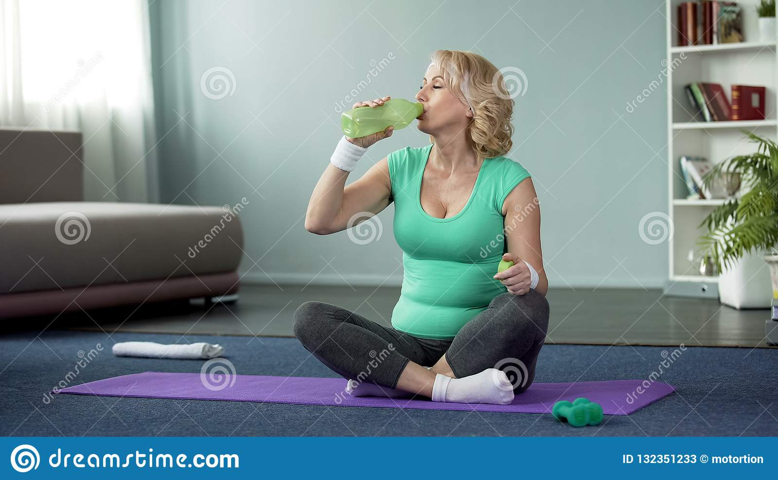 Athletic senior woman sitting on floor and drinking water after workout, health