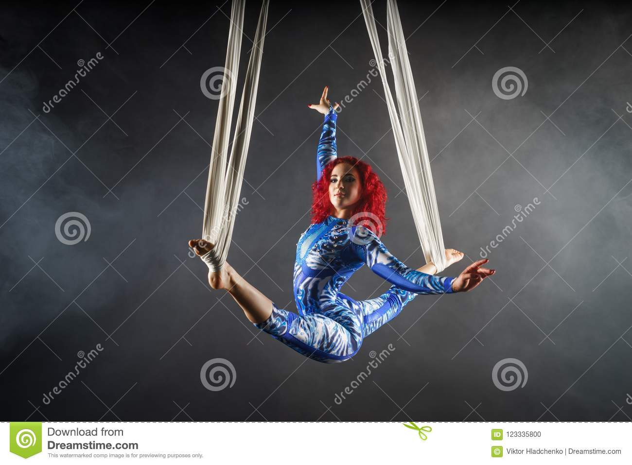 Athletic aerial circus artist with redhead in blue costume dancing in the air with balance