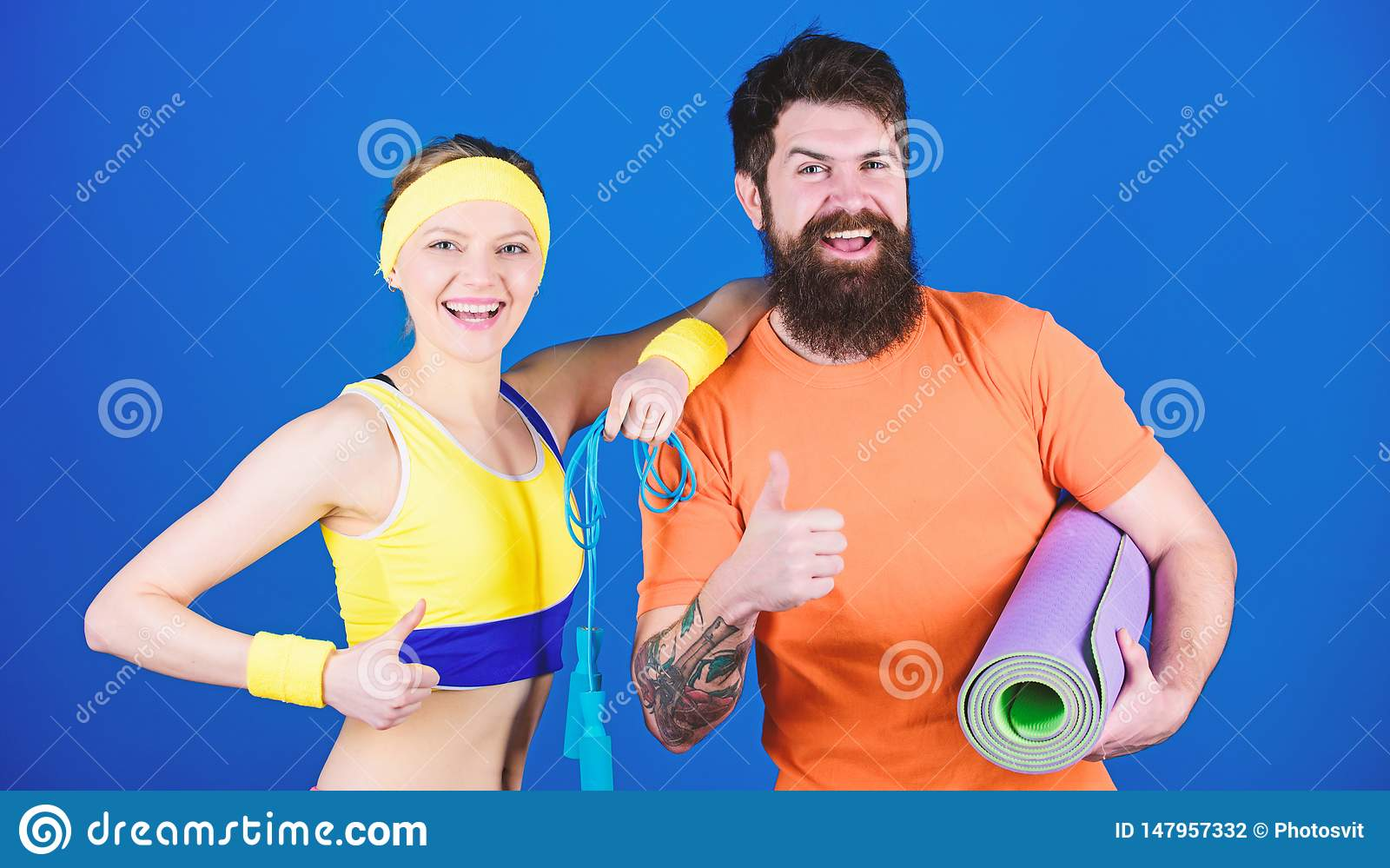 Athletic Success. Sporty couple training with fitness mat and jump rope. Happy woman and bearded man workout in gym