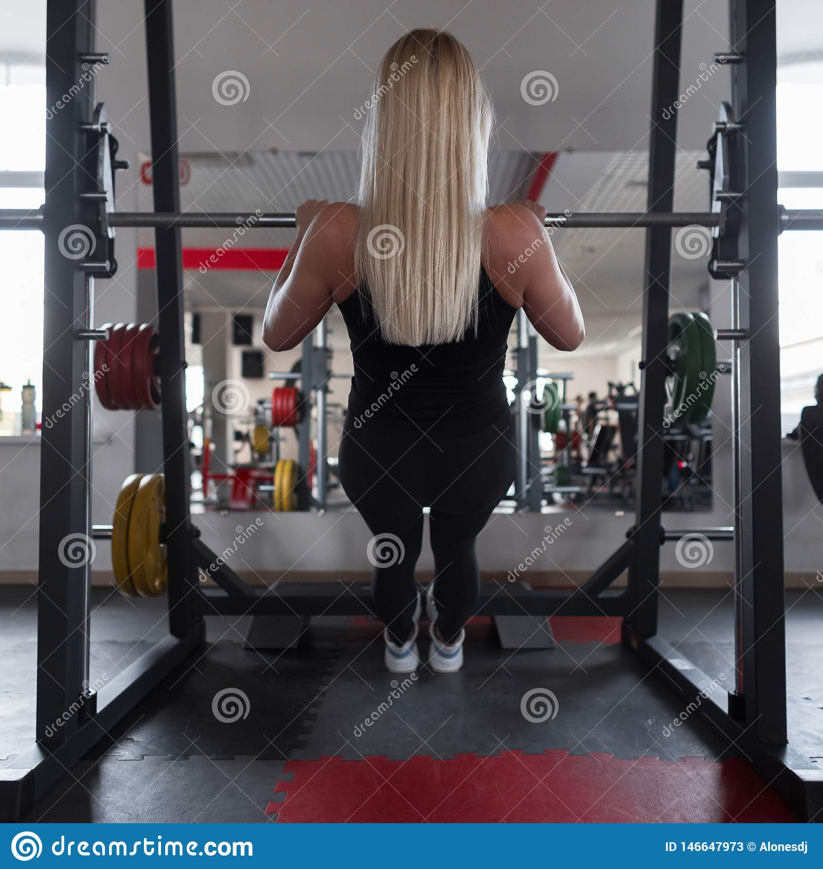 Athletic trainer of a young woman in black sportswear in gym sneakers. Girl doing exercises in a fitness studio. Back view.