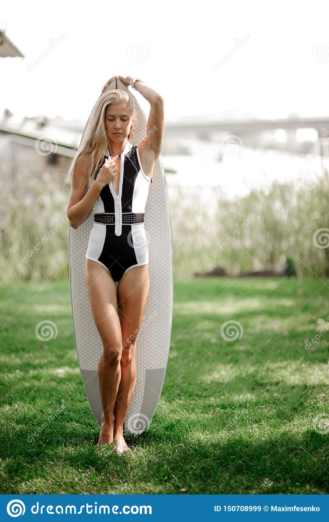 Athletic woman poses with a surfing board