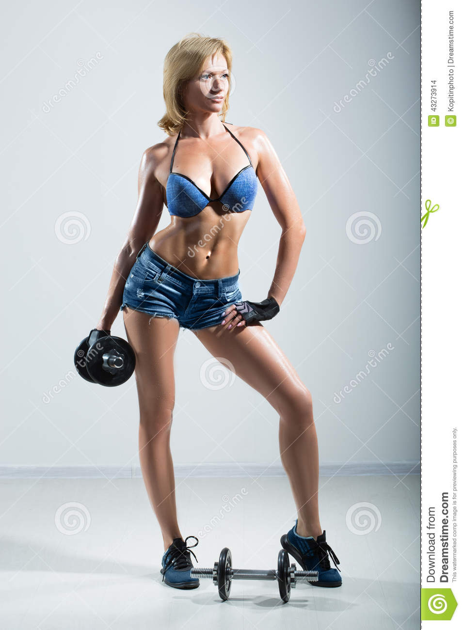 Athletic Woman Pumping Up Muscules With Dumbbells Stock