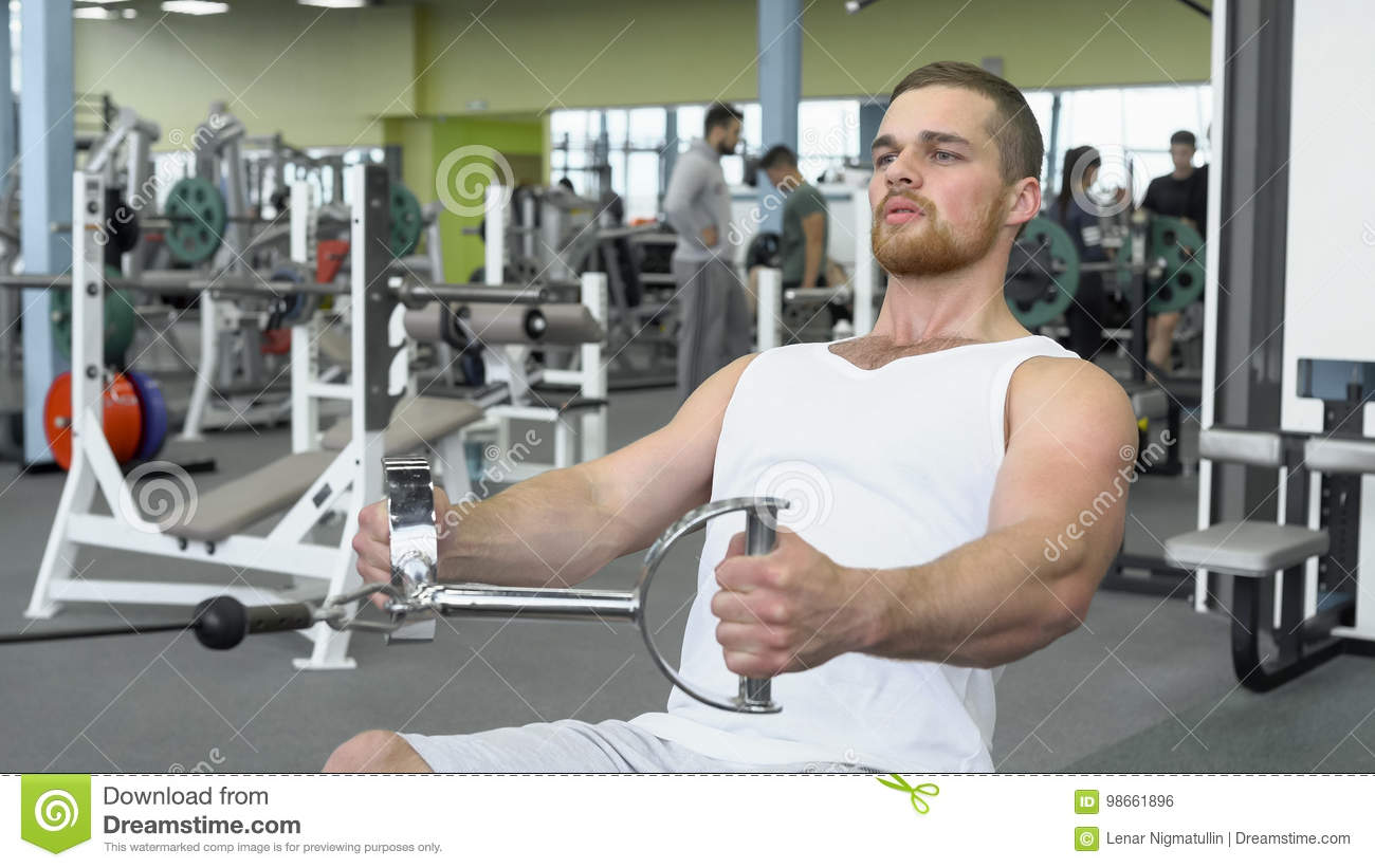 Athletic young man exercising on a block device. Portrait of strong athletic man at the gym training