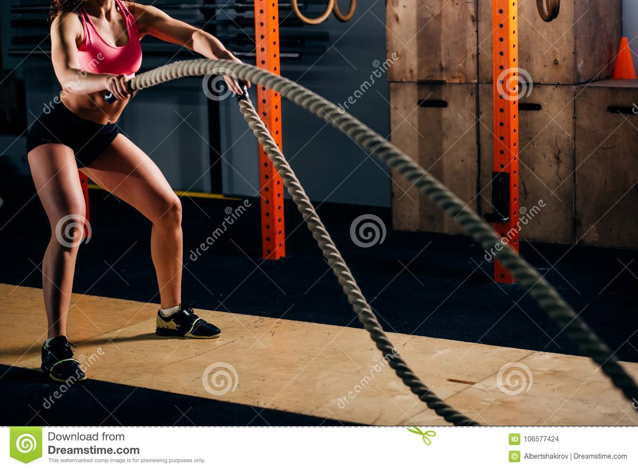 Athletic young woman doing some cross fit exercises with rope outdoor