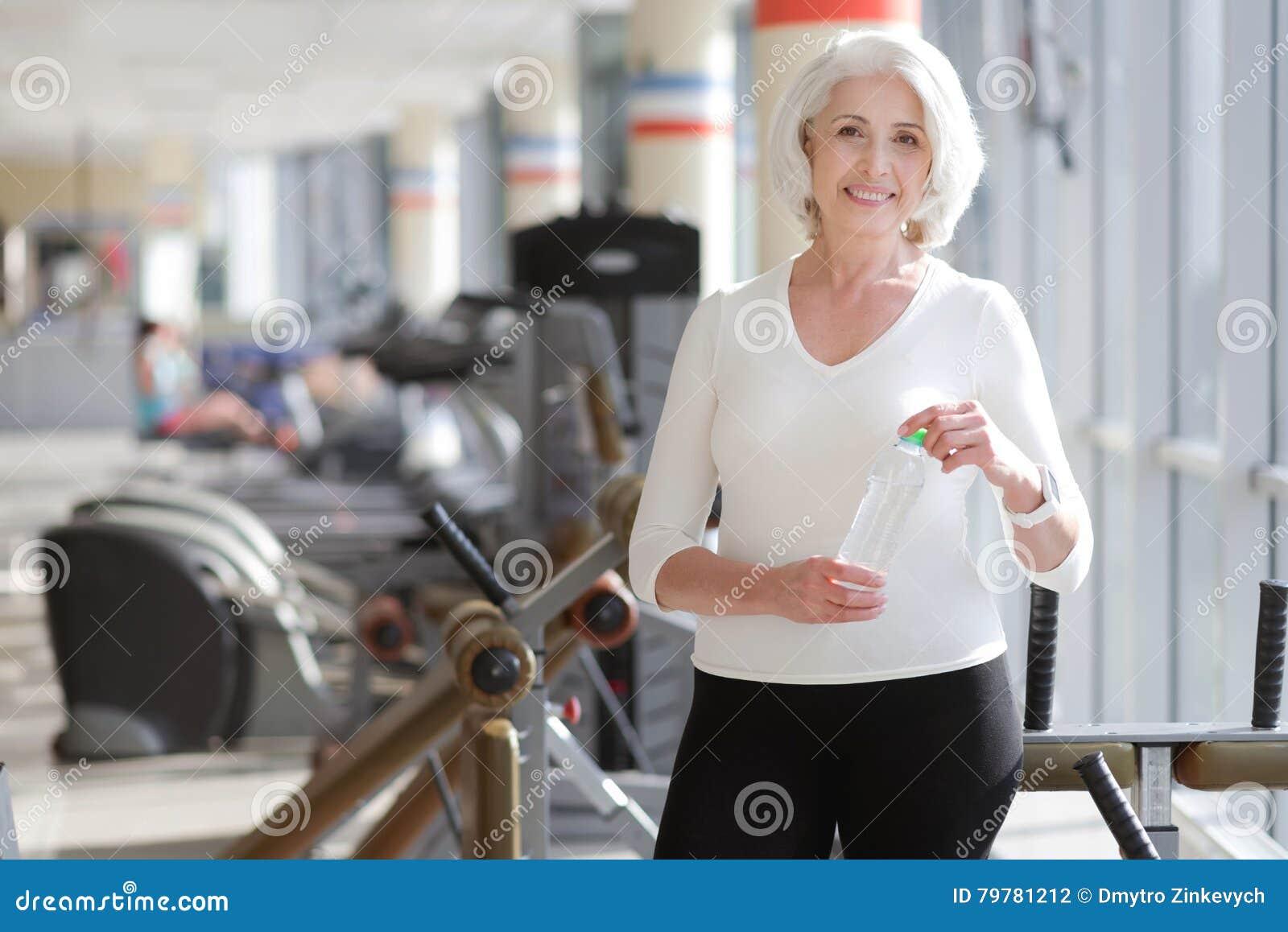 Athletische reizend ältere Frau, die Rest während des Turnhallentrainings hat