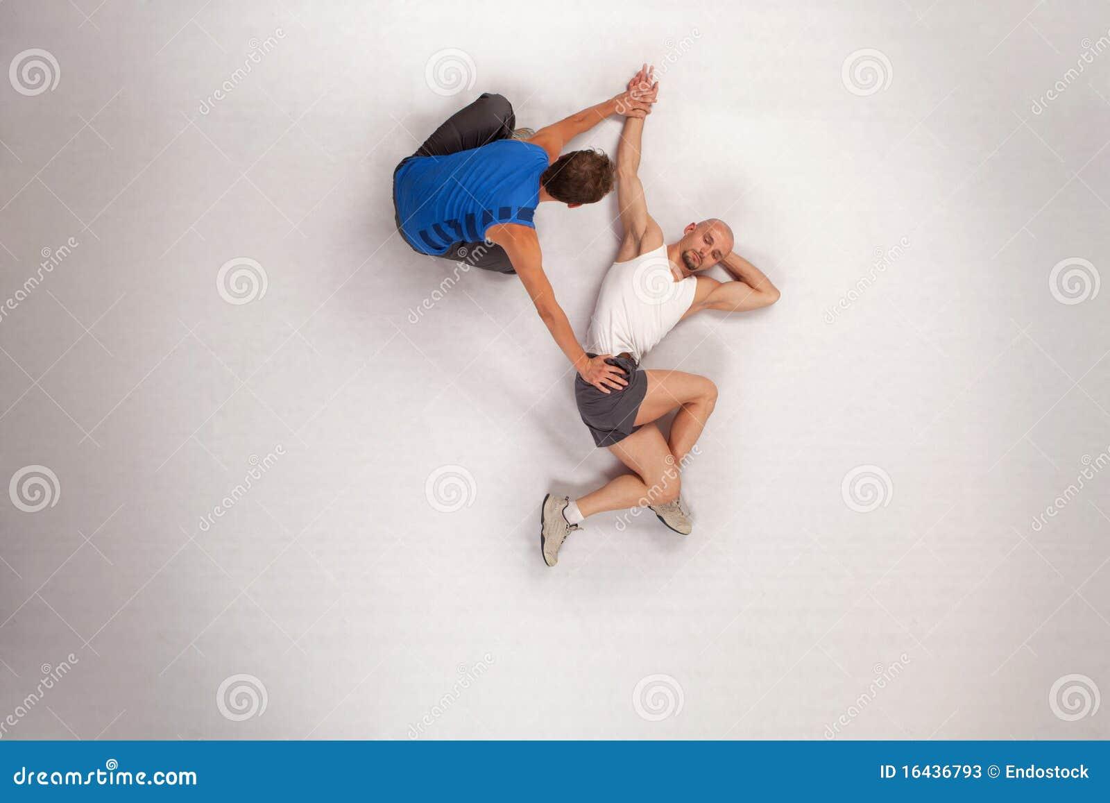 Athletischer Mann, der mit persönlichem Kursleiter streching ist