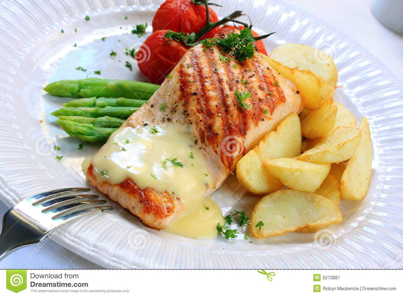 salmon fillet, served with asparagus, potato wedges, truss tomatoes ...