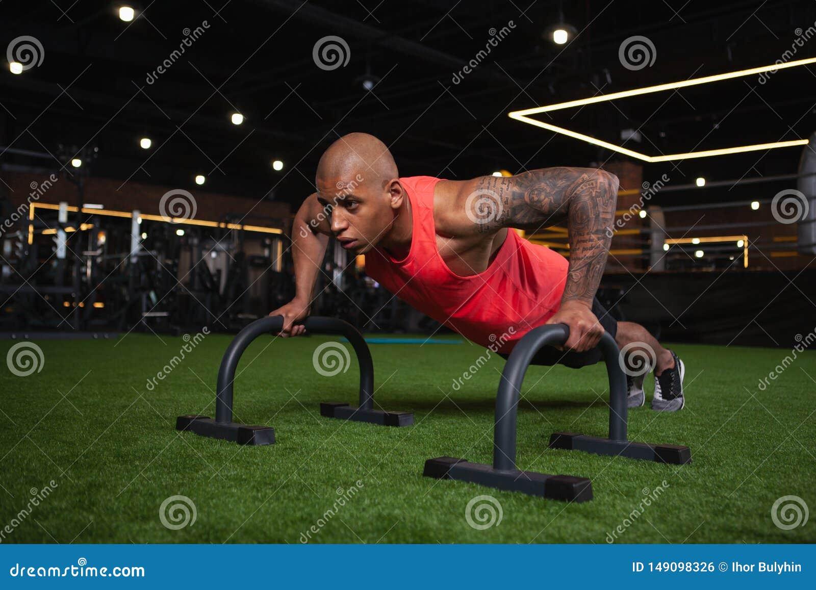 Atleta africano de sexo masculino hermoso que se resuelve en el gimnasio