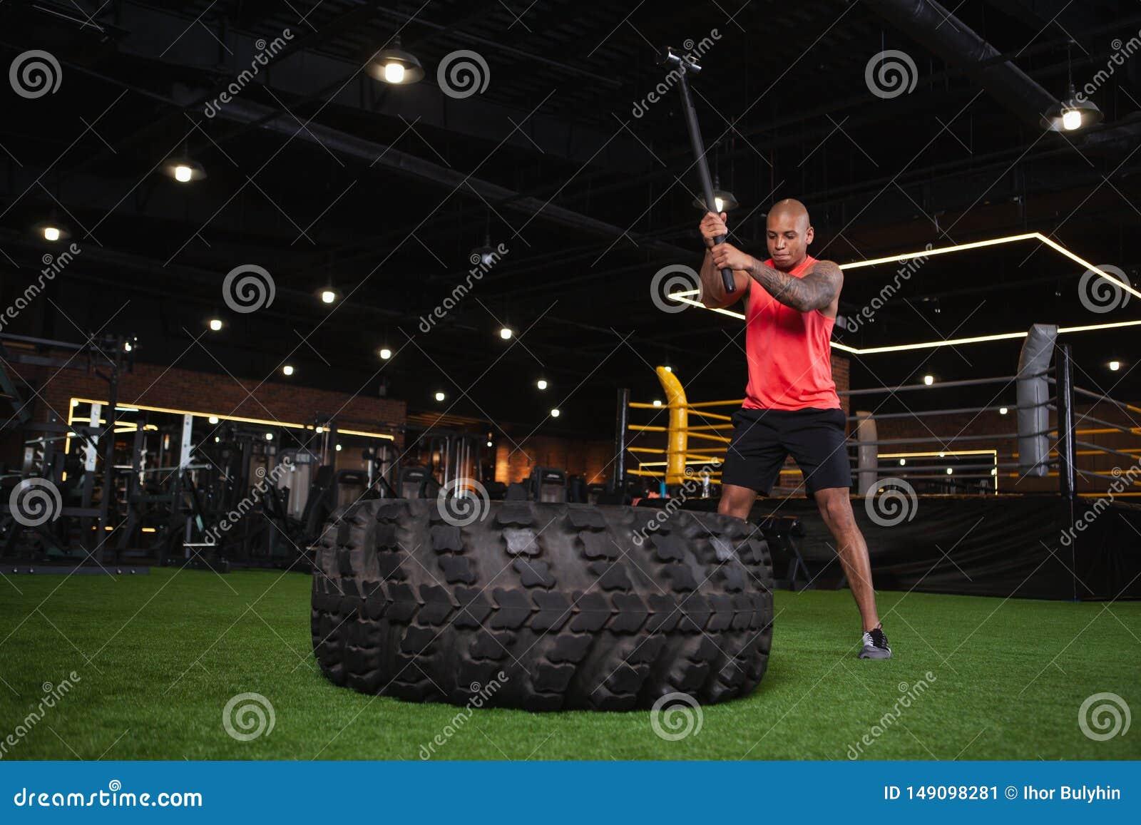 Atleta africano maschio bello che risolve alla palestra