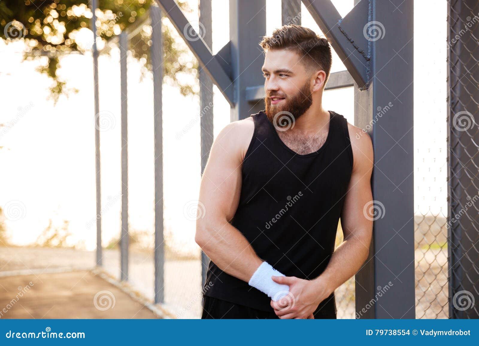 Atleta barbudo sonriente que se coloca al aire libre y que mira lejos