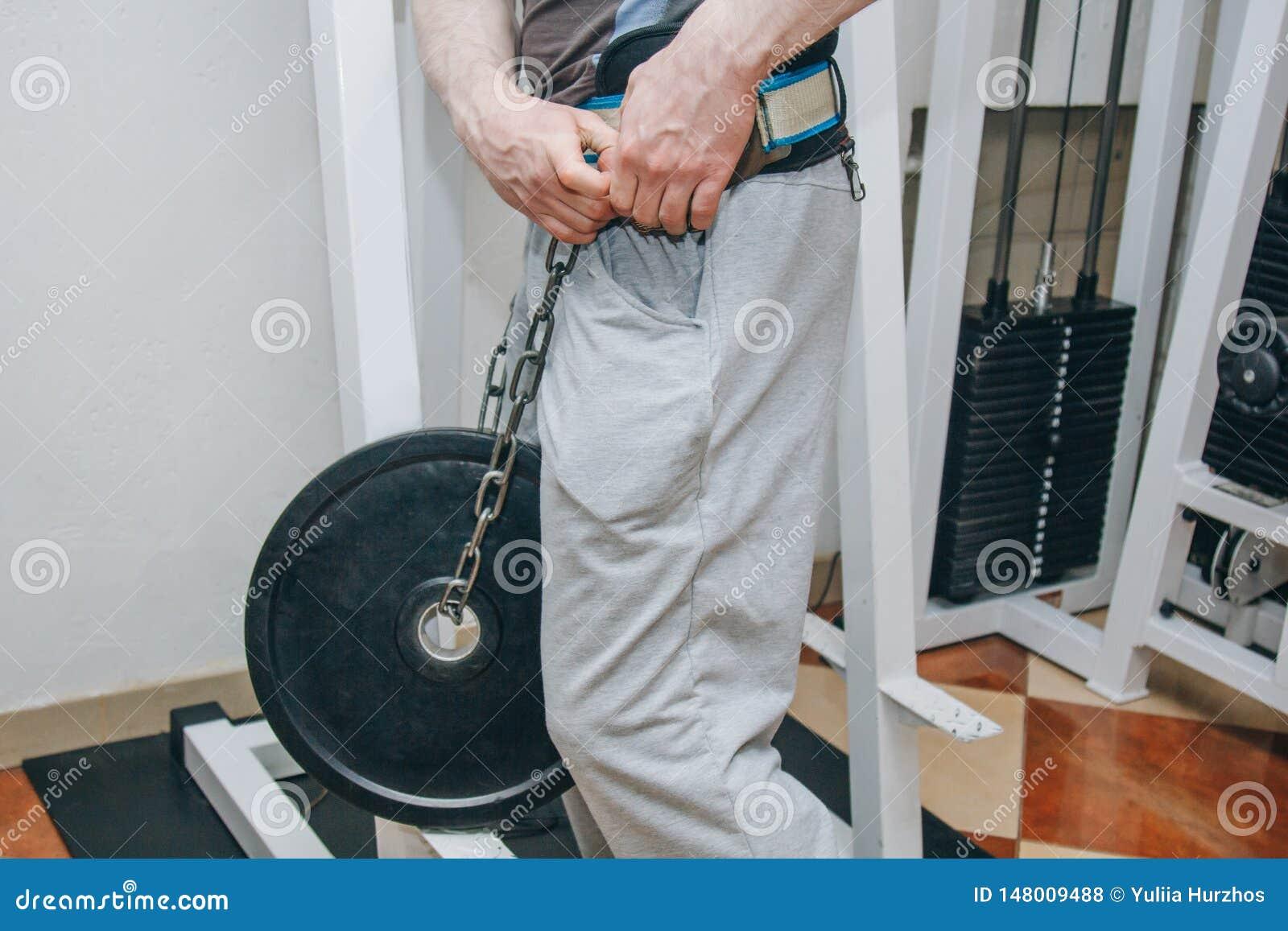 Atleta che fa esercizio con peso sulla cinghia di vita nel centro di addestramento strumenti di formazione nel primo piano della