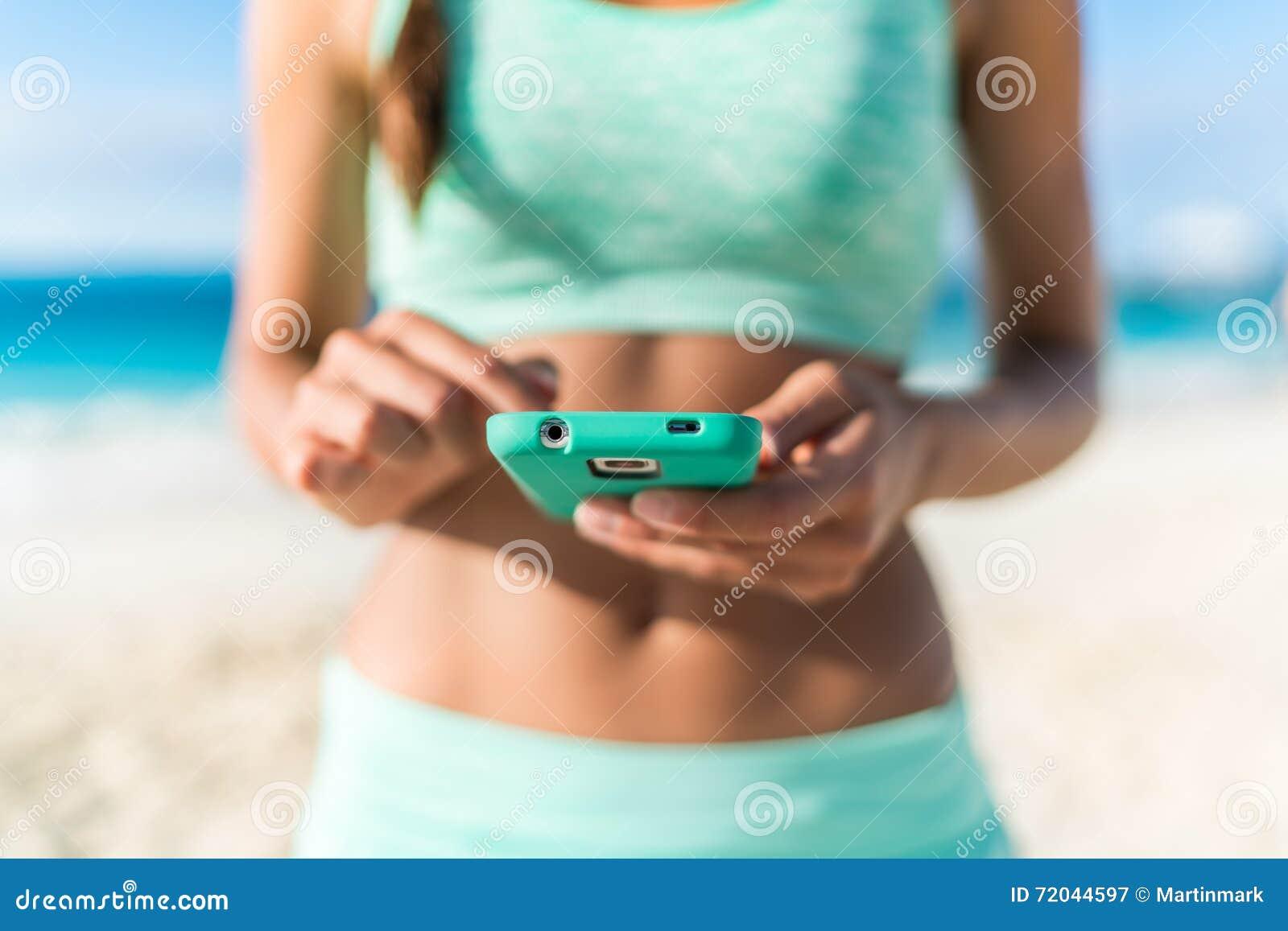 Atleta che usando allenamento della spiaggia dello smartphone di app di forma fisica