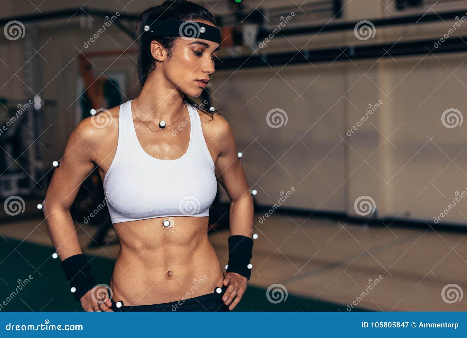 Atleta de sexo femenino con los sensores de la captura de movimiento en laboratorio de la biomecánica