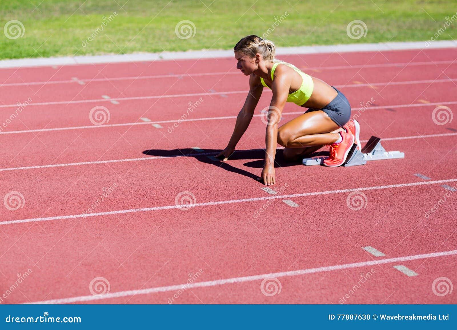 Atleta De Sexo Femenino Listo Para Correr En Pista Corriente Foto de archivo
