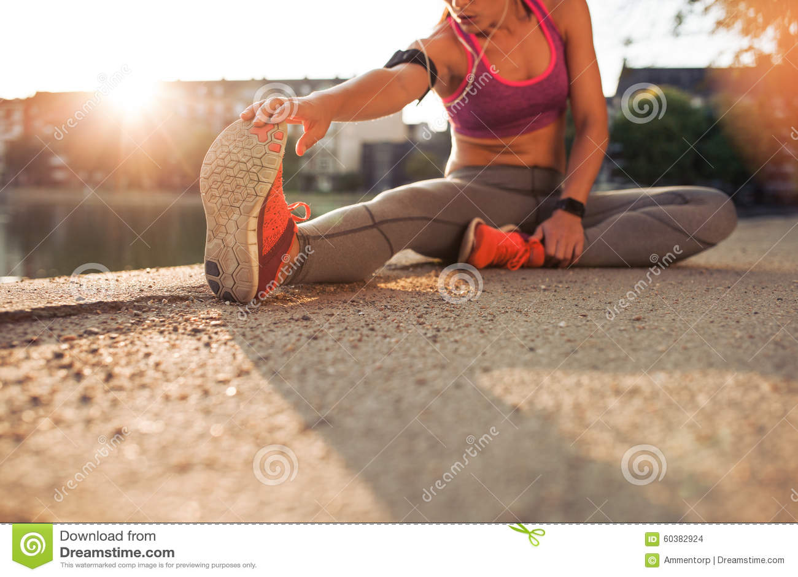 Atleta de sexo femenino que estira las piernas