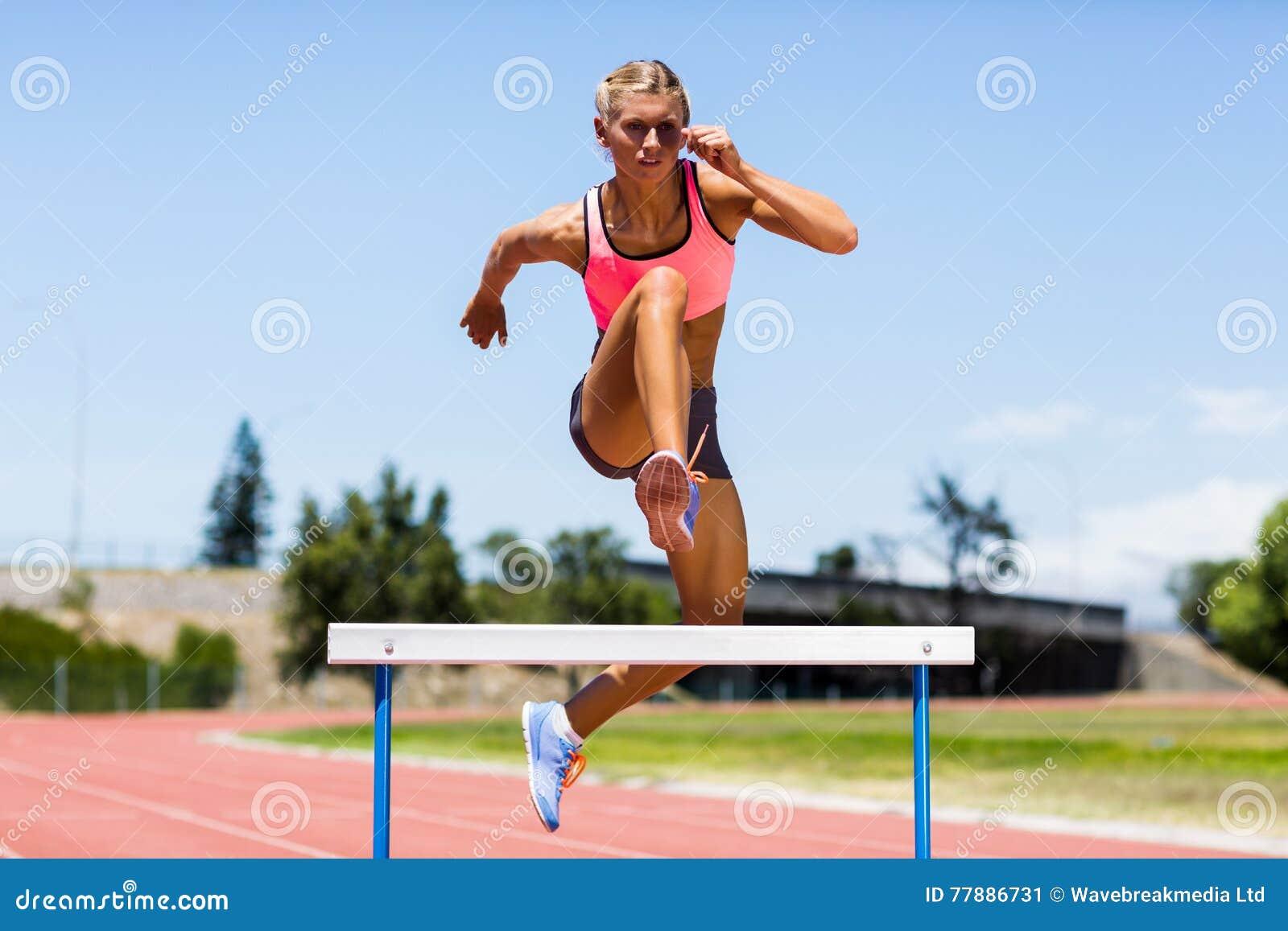 Atleta De Sexo Femenino Que Salta Sobre El Obstáculo Foto de archivo