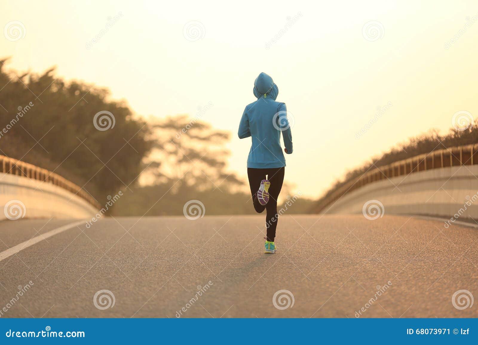 Atleta del corredor de la mujer de la aptitud que corre en el camino de la salida del sol