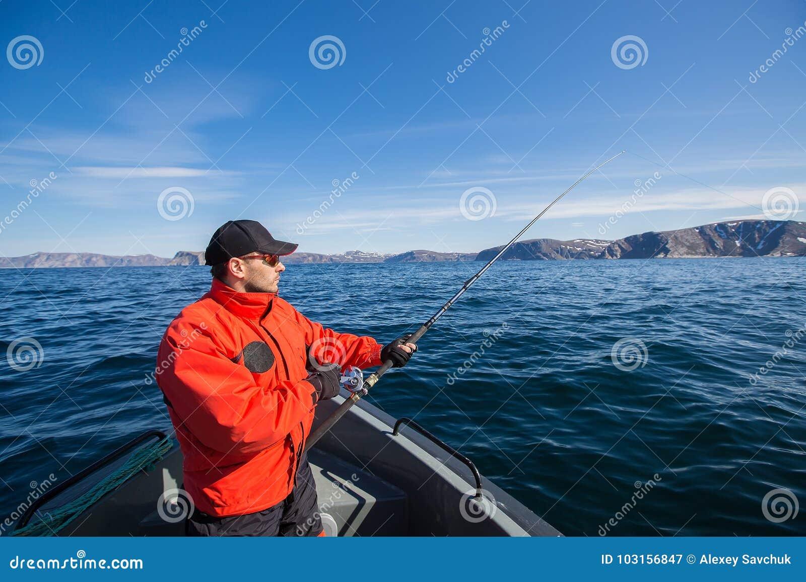 Atleta del pescatore con una canna da pesca in sue mani Una barca Sea