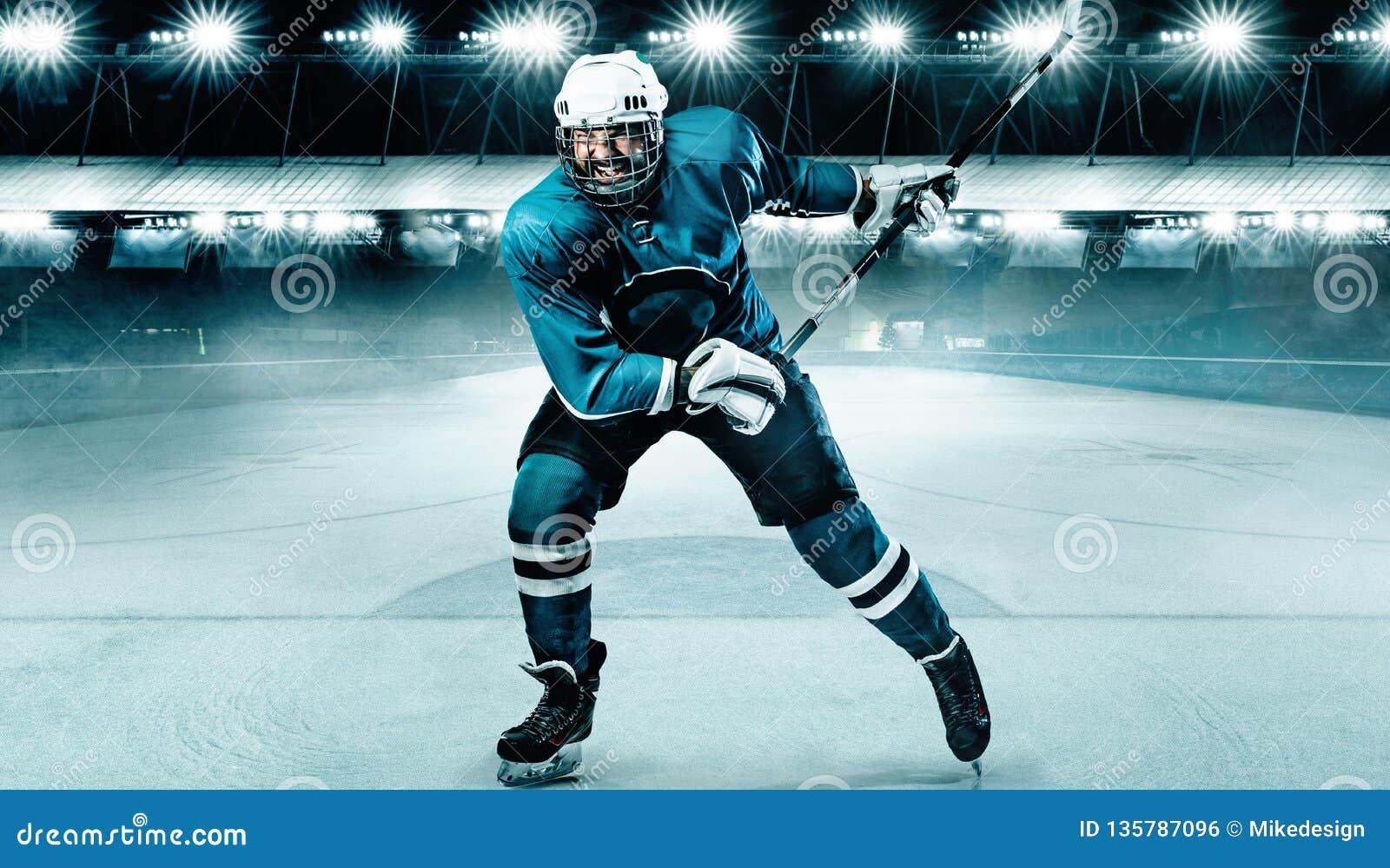 Atleta do jogador de hóquei em gelo no capacete e luvas no estádio com vara Tiro da ação Conceito do esporte