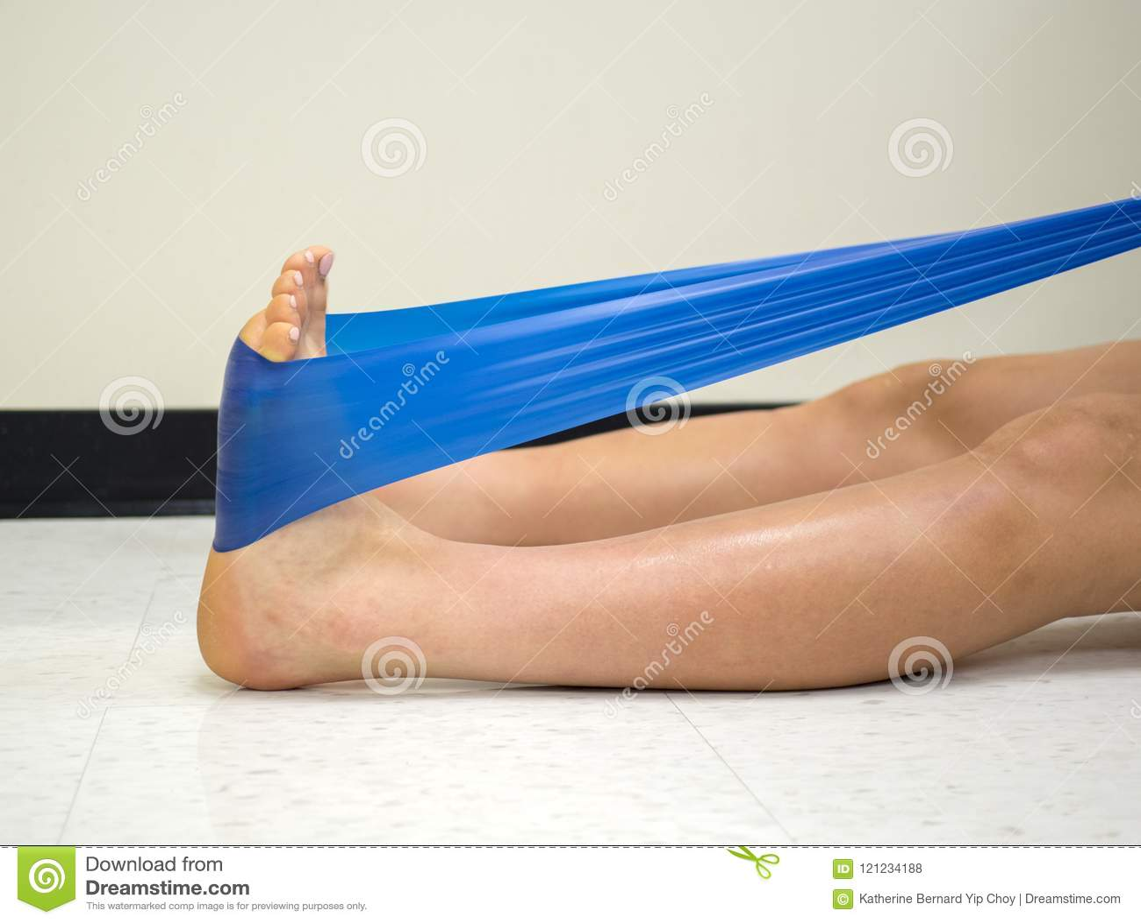 Atleta do time do colégio que usa uma faixa do exercício do theraband para reforçar seu tornozelo