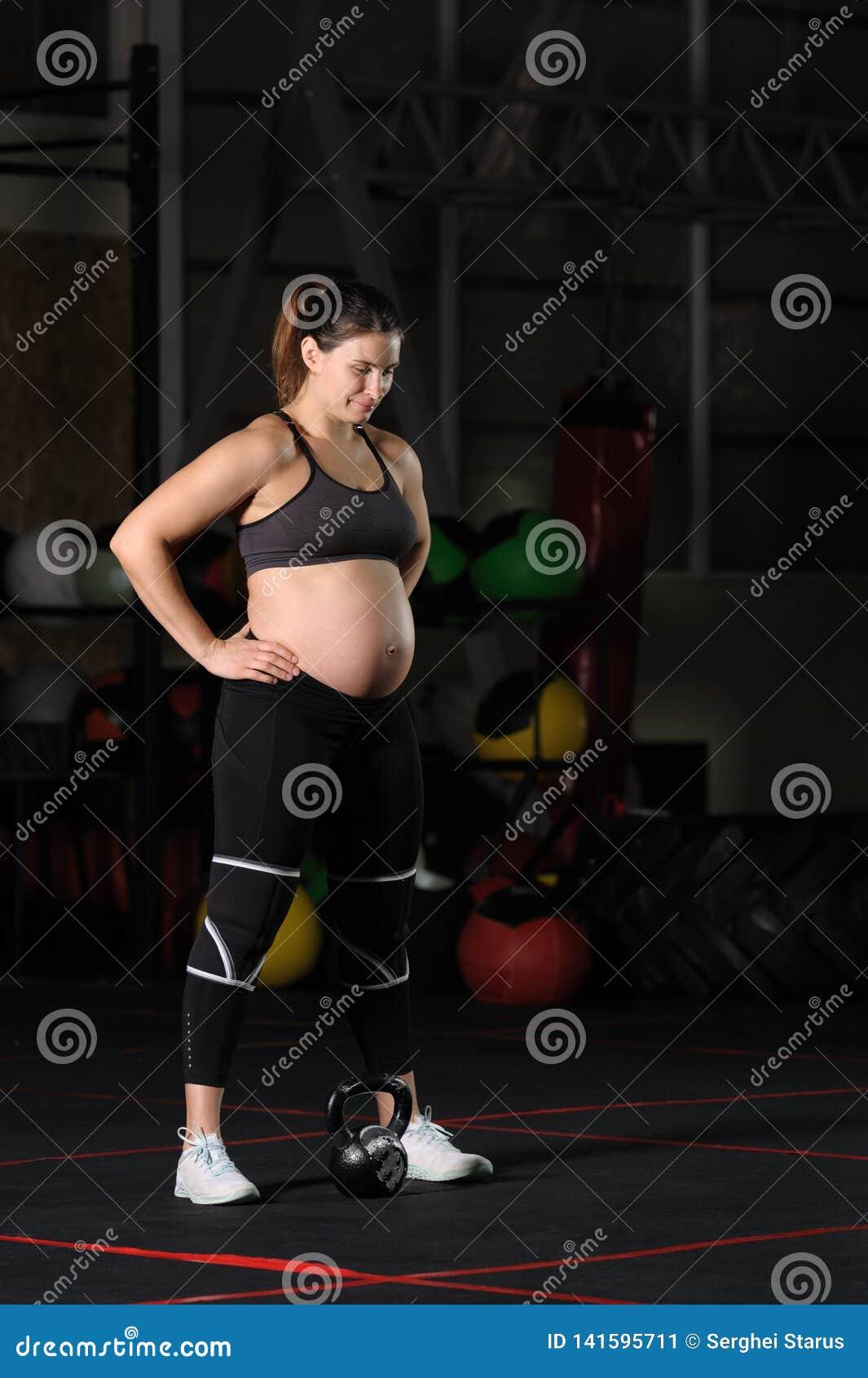 Atleta fêmea grávido que faz o ato de agarrar do poder do peso