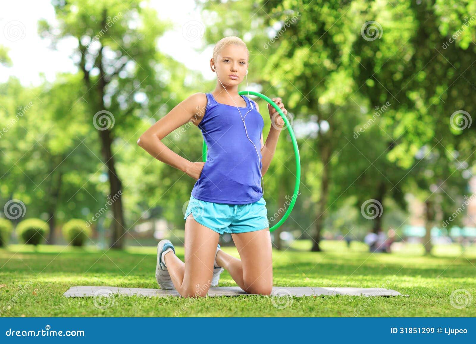 Atleta fêmea novo em uma esteira que guarda uma aro do hula em um parque
