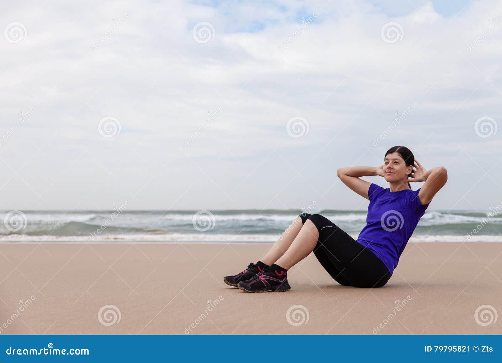 Atleta femminile che esegue situps alla spiaggia
