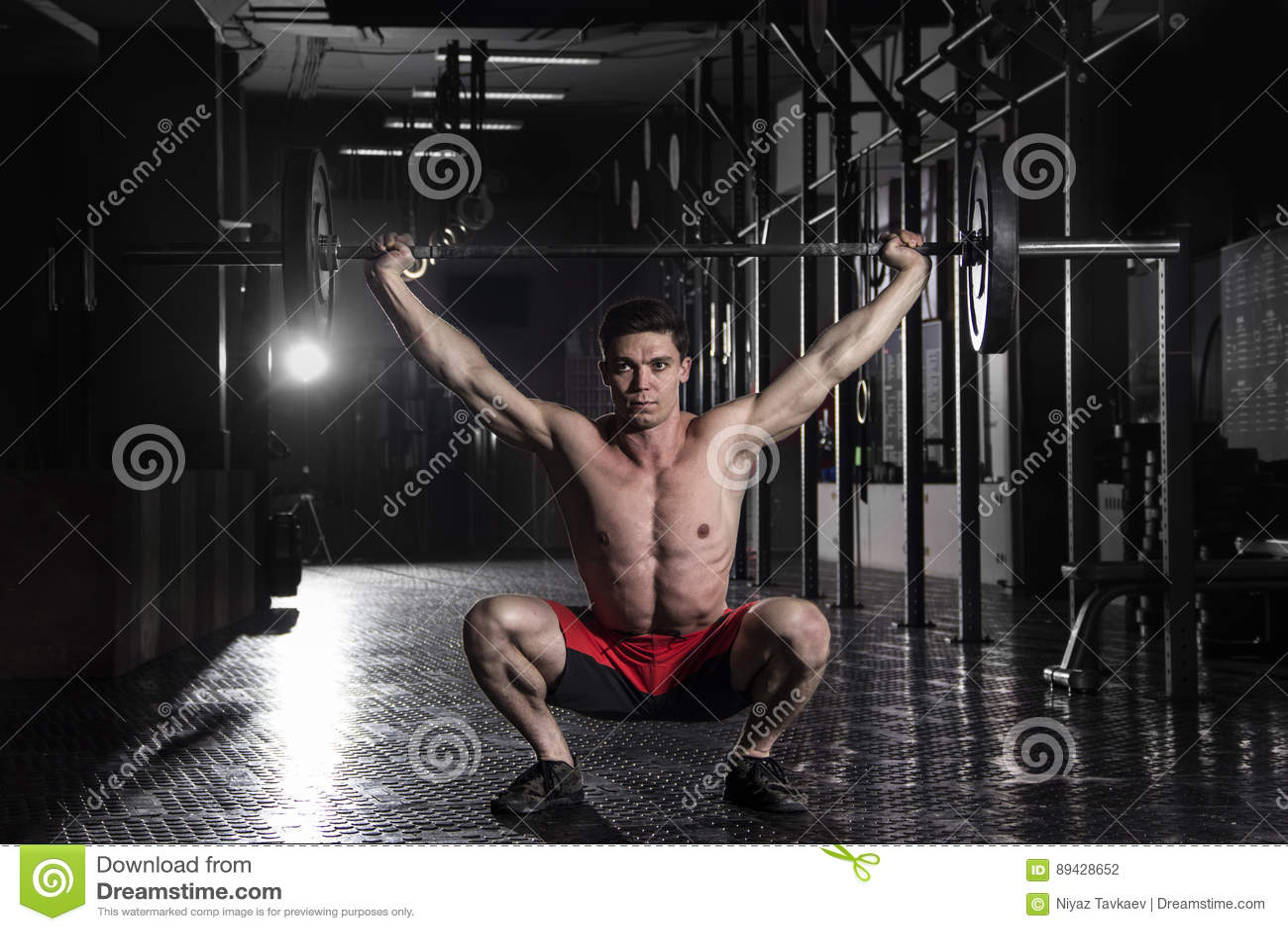 Atleta muscular que hace el exerise del crossfit en el gimnasio El hacer