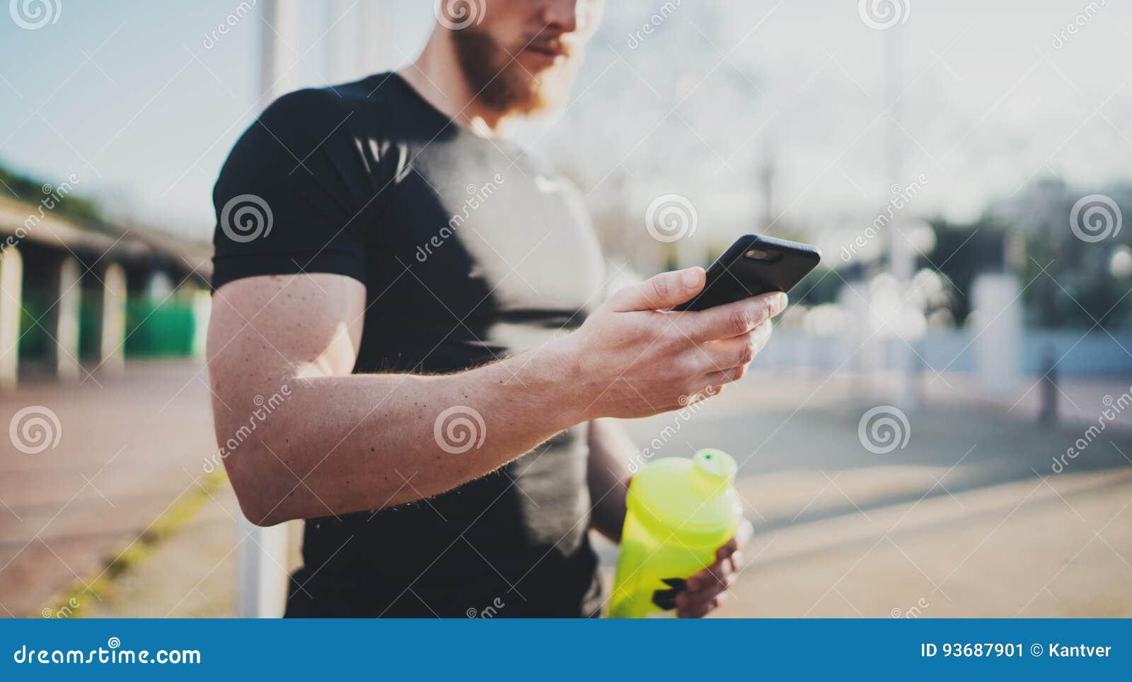 Atleta novo muscular que verifica calorias queimadas na aplicação do smartphone após a sessão exterior do bom exercício em ensola