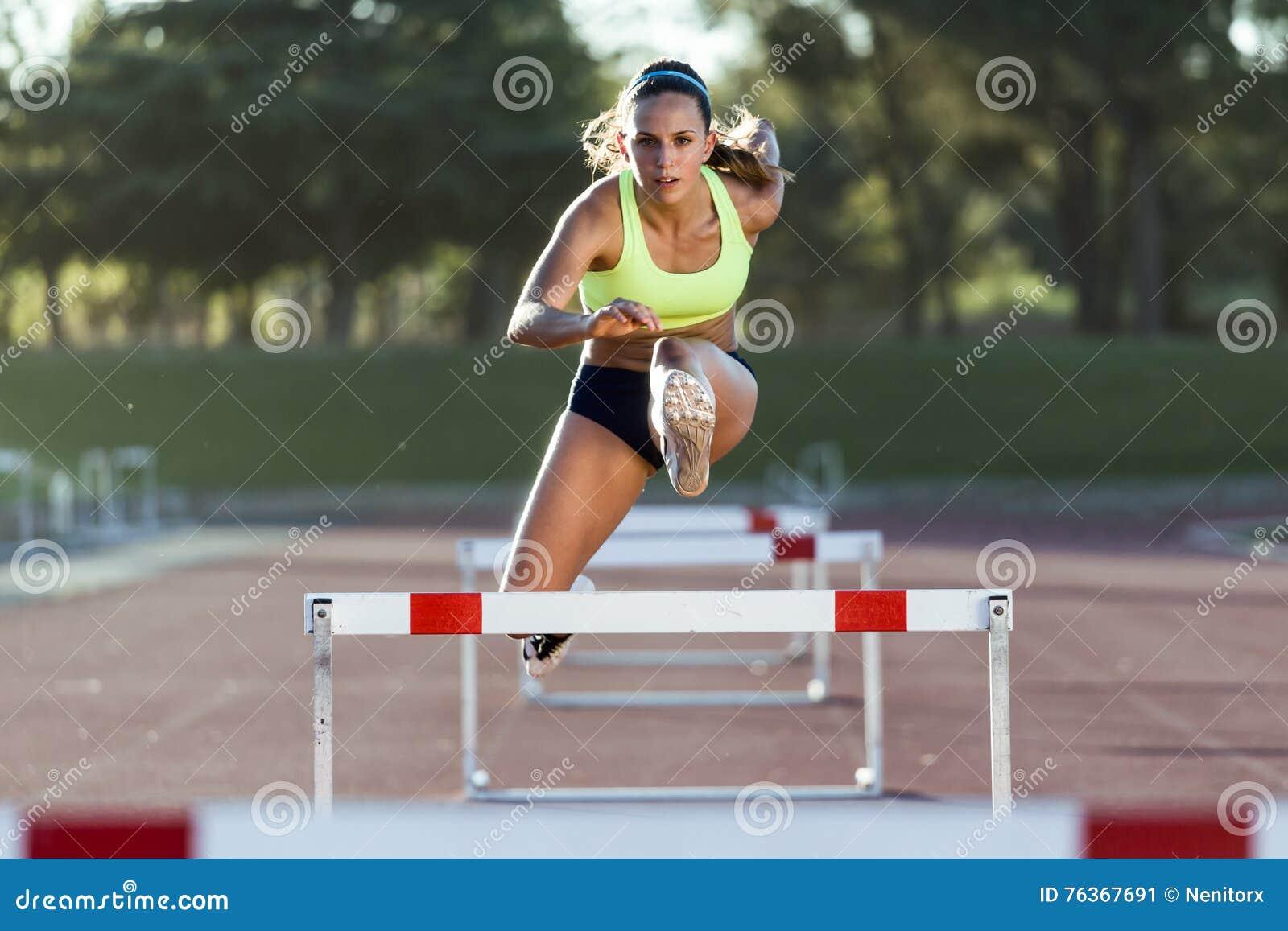 Atleta novo que salta sobre um obstáculo durante o treinamento no trac da raça