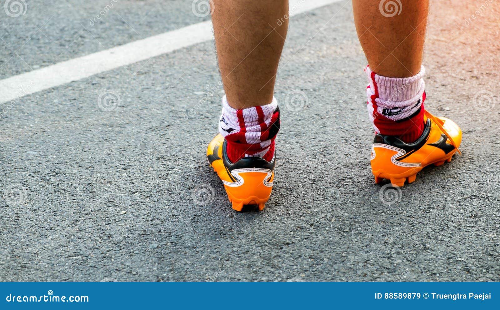 Atleta que corre en el camino, el cierre encima de pies con las zapatillas deportivas y el st