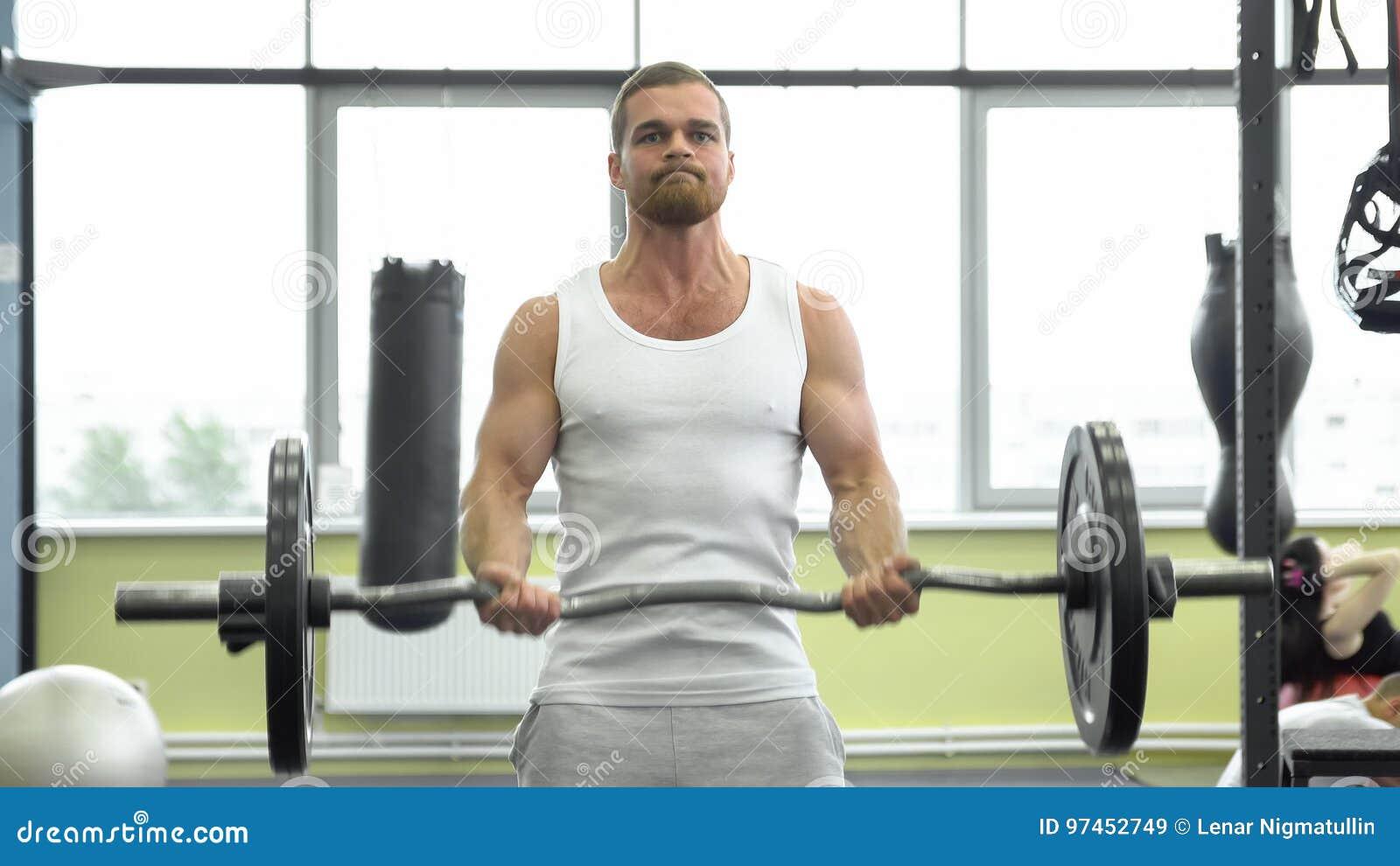 Atleta que hace el ejercicio para el bíceps con el barbell Trenes musculares jovenes del hombre en el gimnasio Entrenamiento de C