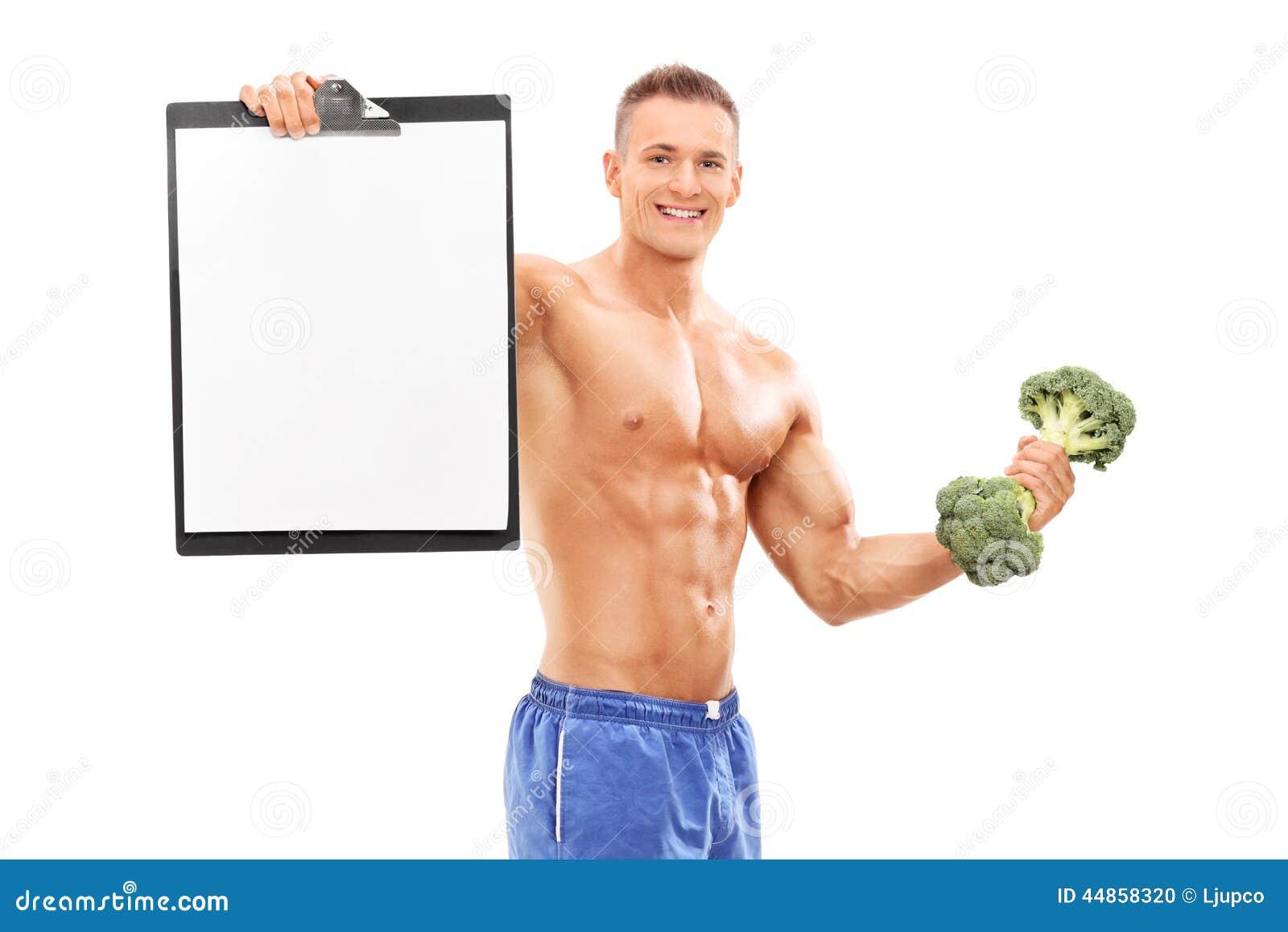 Atleta que lleva a cabo el tablero y una pesa de gimnasia del bróculi