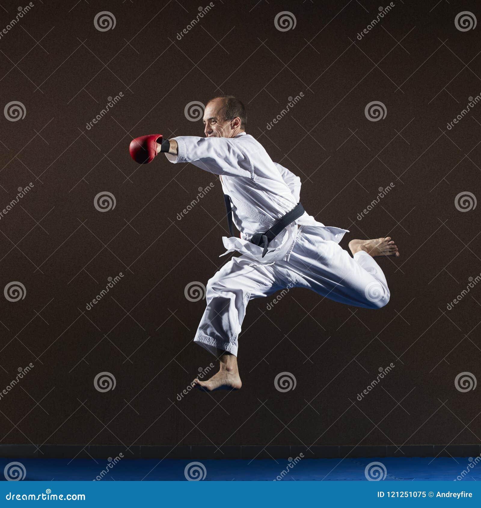 Atleta z czerwonymi narzutami na jego rękach bije cios z jego ręką w skoku