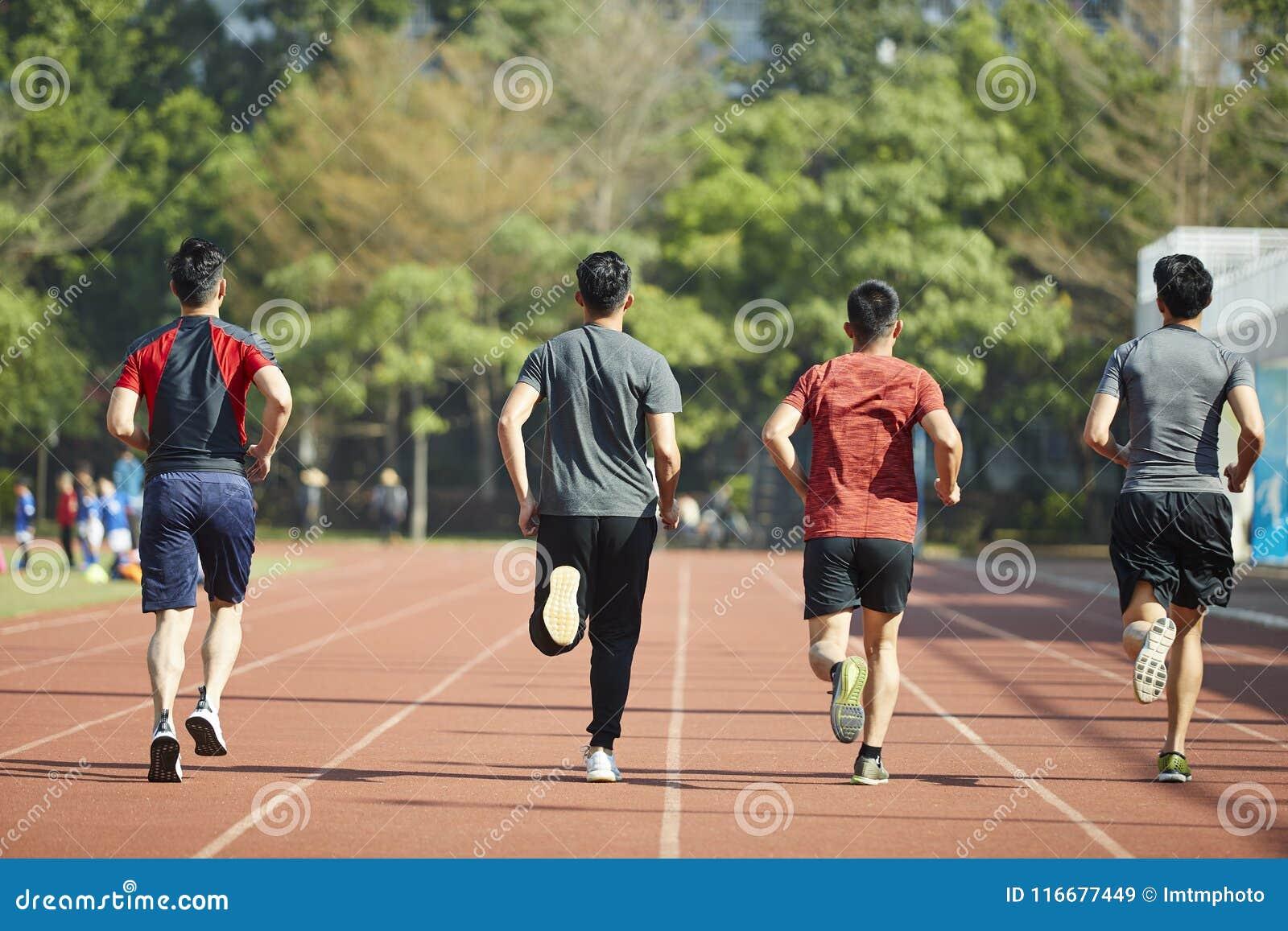Atletas asiáticos jovenes que corren en pista
