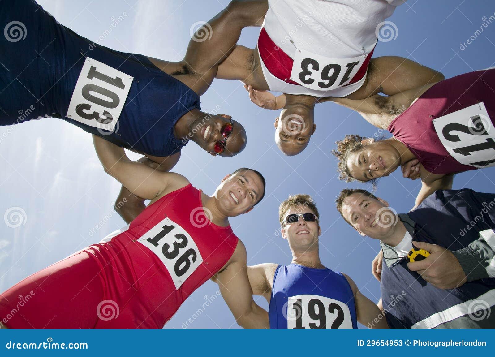 Atletas com instrutor Forming uma aproximação