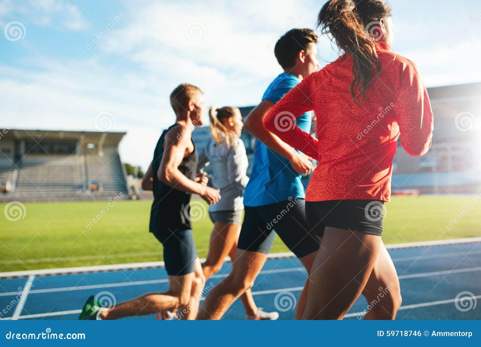 Atletas jovenes que corren en circuito de carreras en estadio