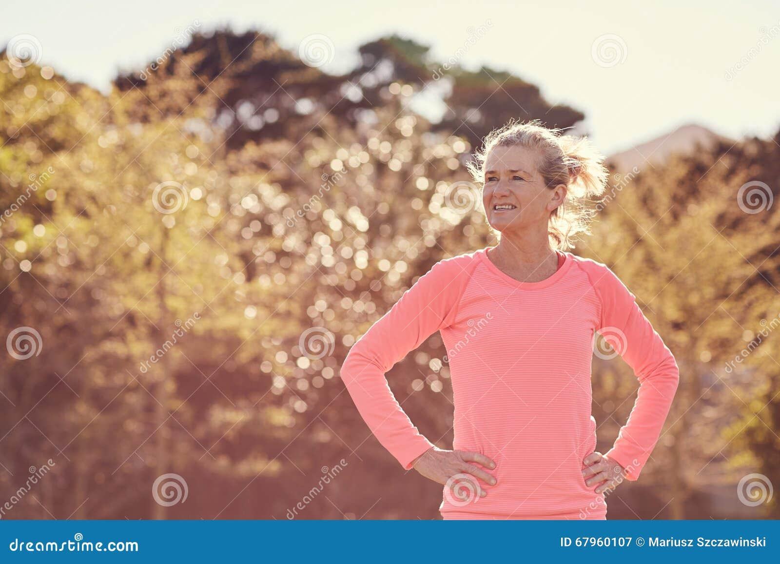 Atletische hogere vrouw die zeker in openlucht op zonovergoten mor kijkt