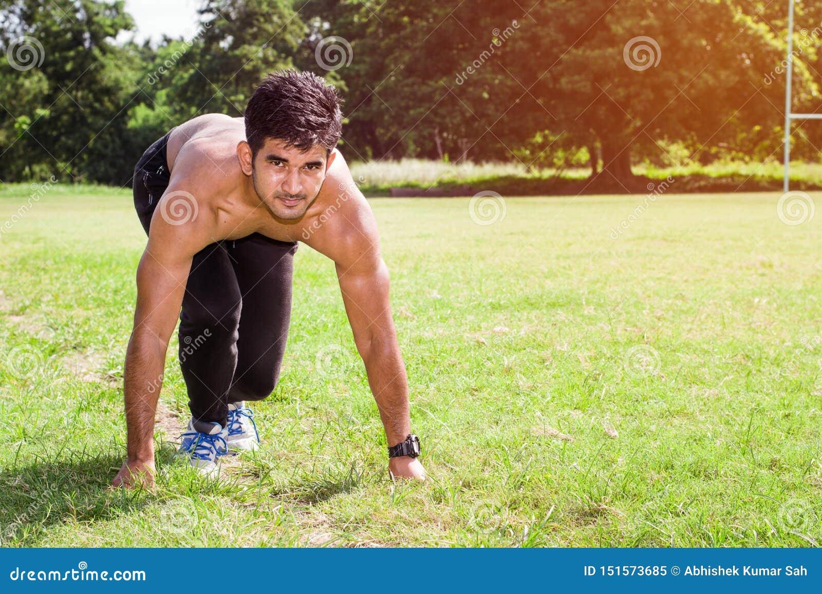 Atletische jonge mens die in de sportengrond lopen Gezond levensstijl, fitness en sportenconcept