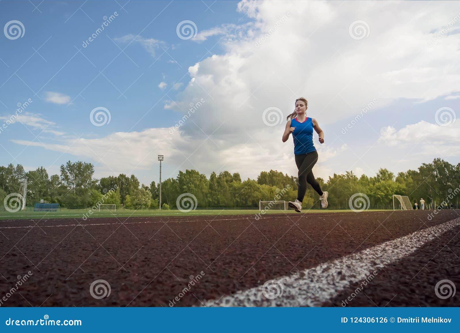 Atletische jonge sportvrouw die op renbaanstadion sprinten