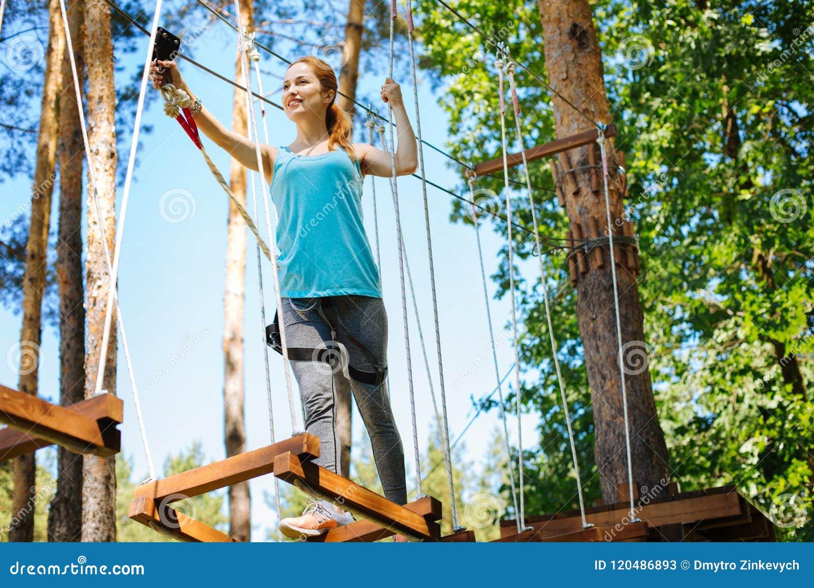 Atletische jonge vrouw die zich langs de sleep van het kabelpark bewegen