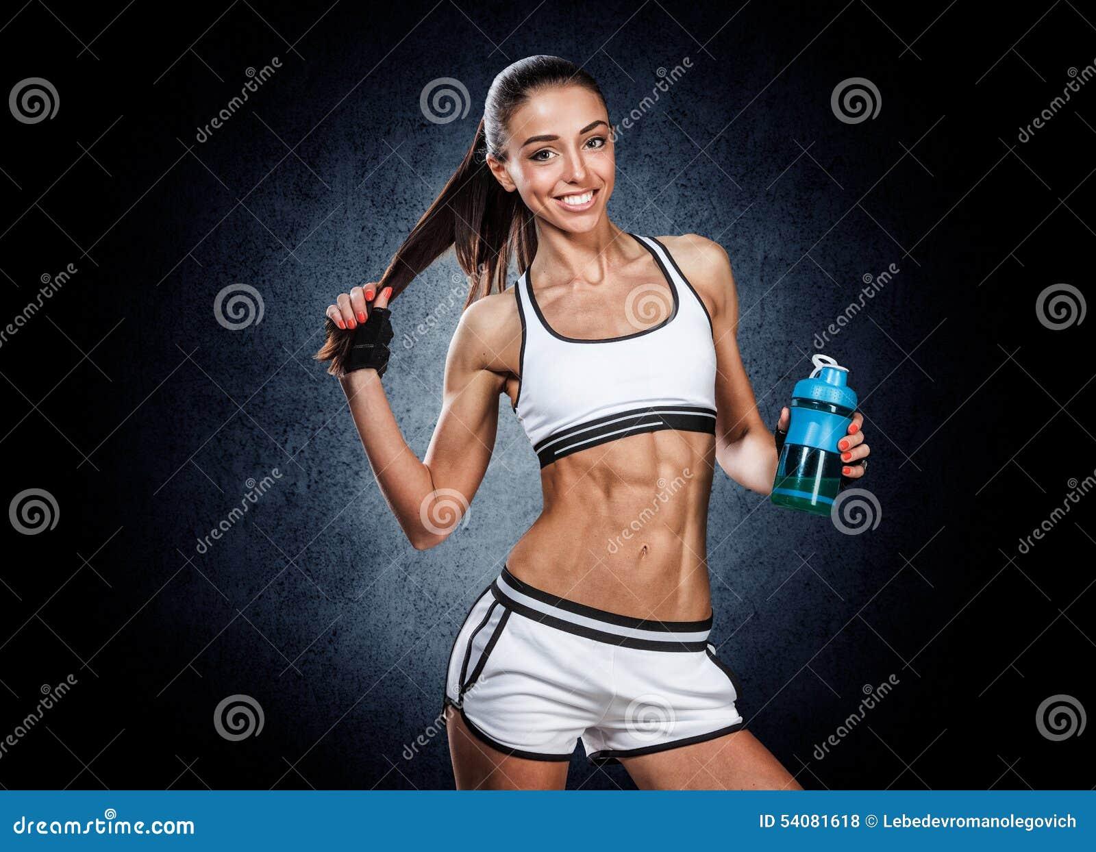 Atletische jonge vrouw met waterfles ter beschikking op een zwarte backgr
