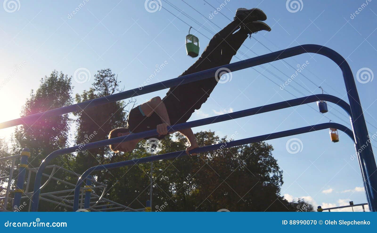 Atletische mens die gymnastiekelementen op bar in stadspark doen De mannelijke sportman voert sterkteoefeningen tijdens training