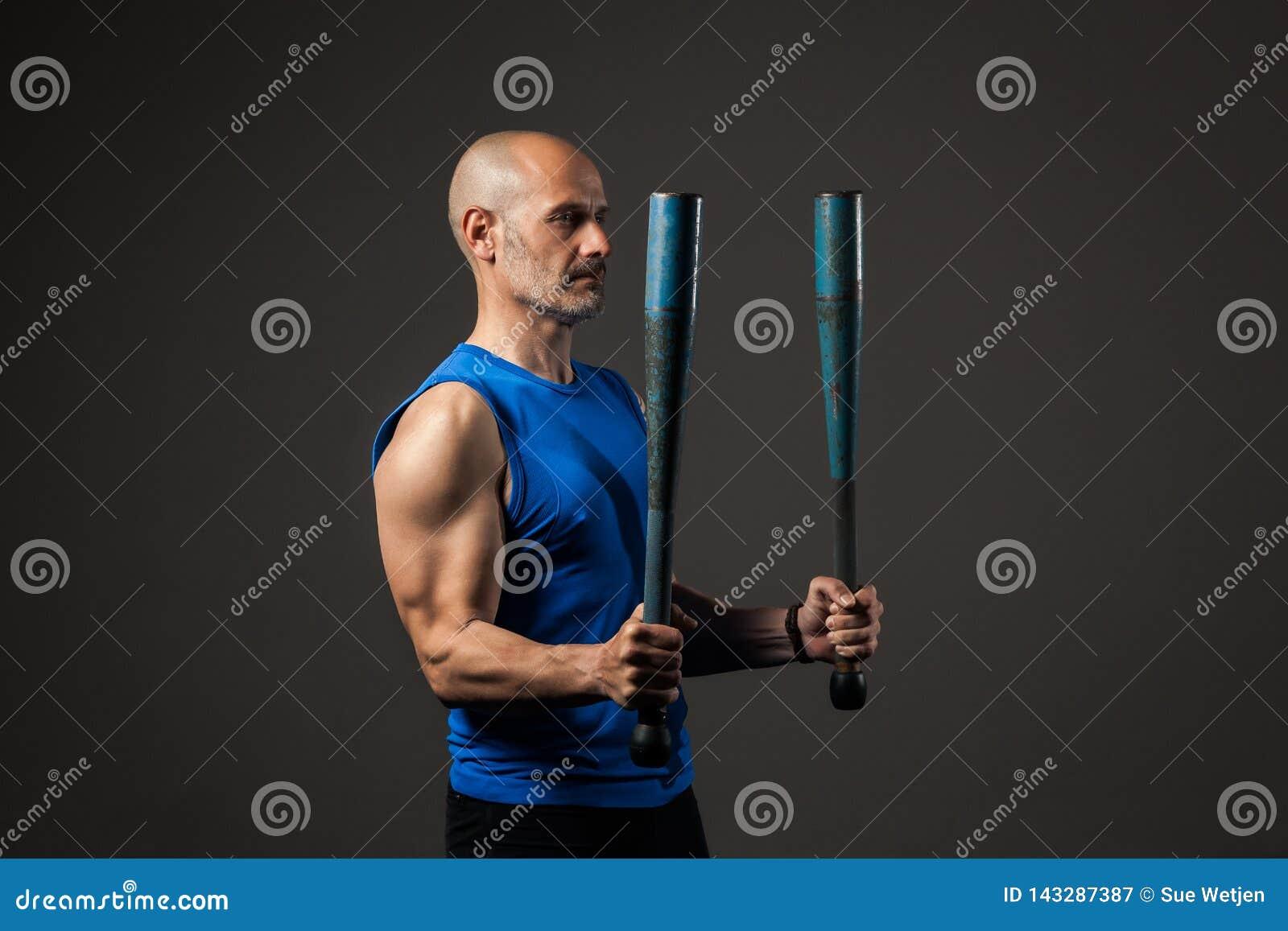 Atletische, midden oude mens opleiding met clubbells, studioachtergrond