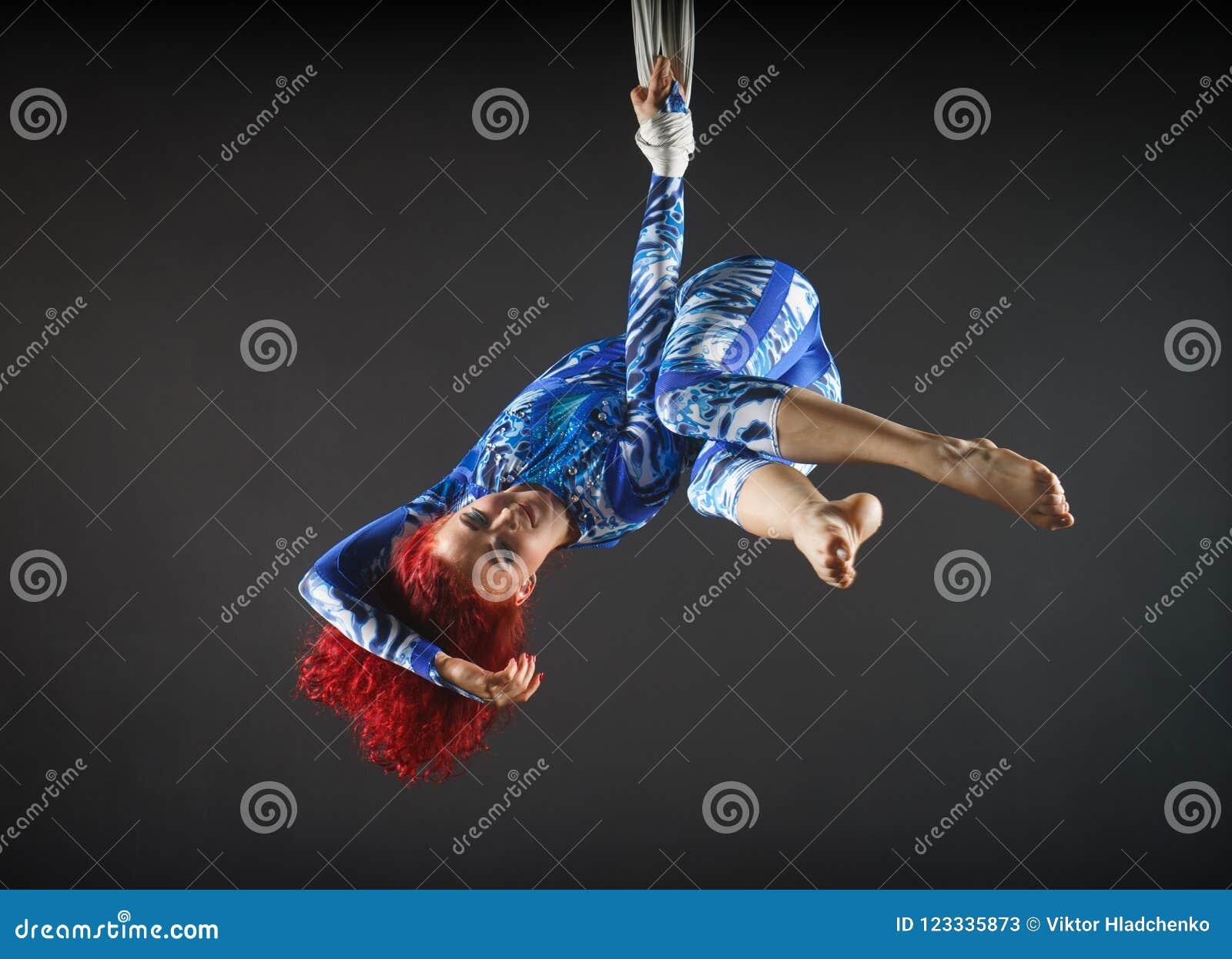 Atletische sexy luchtcircuskunstenaar met roodharige in blauw kostuum die in de lucht met saldo dansen