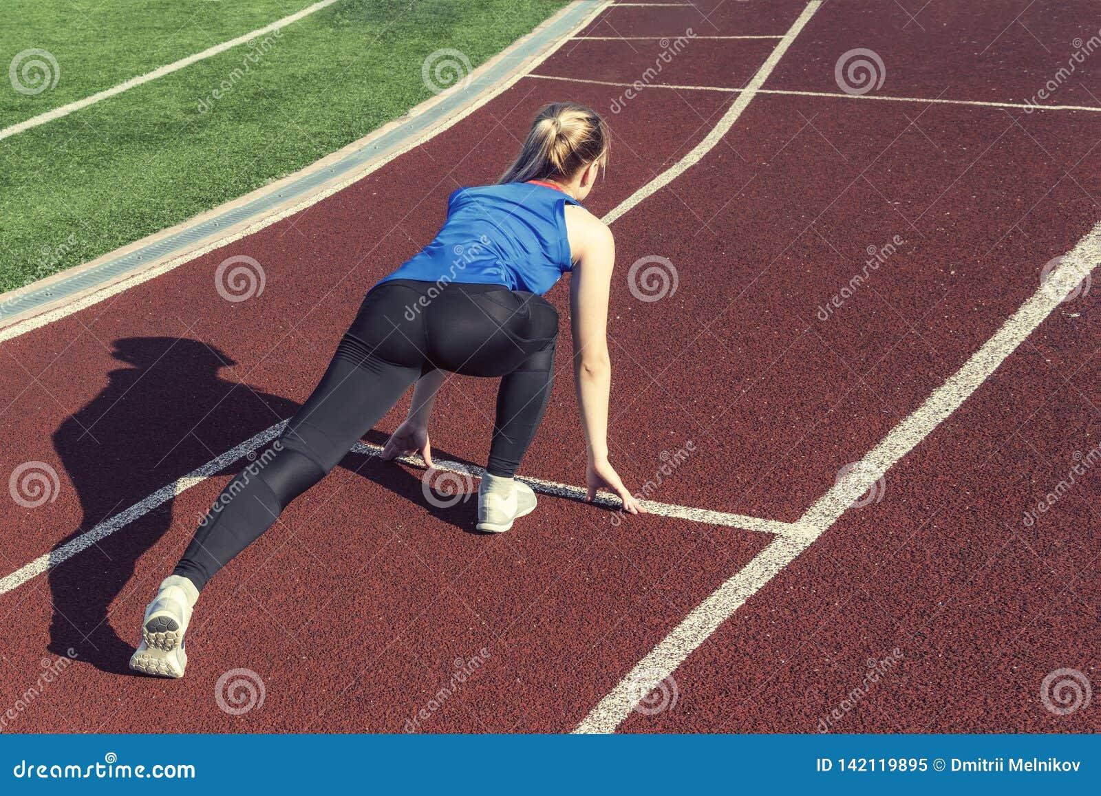 Atletische tiener in beginpositie inzake spoor Concept zich vooruit het bewegen
