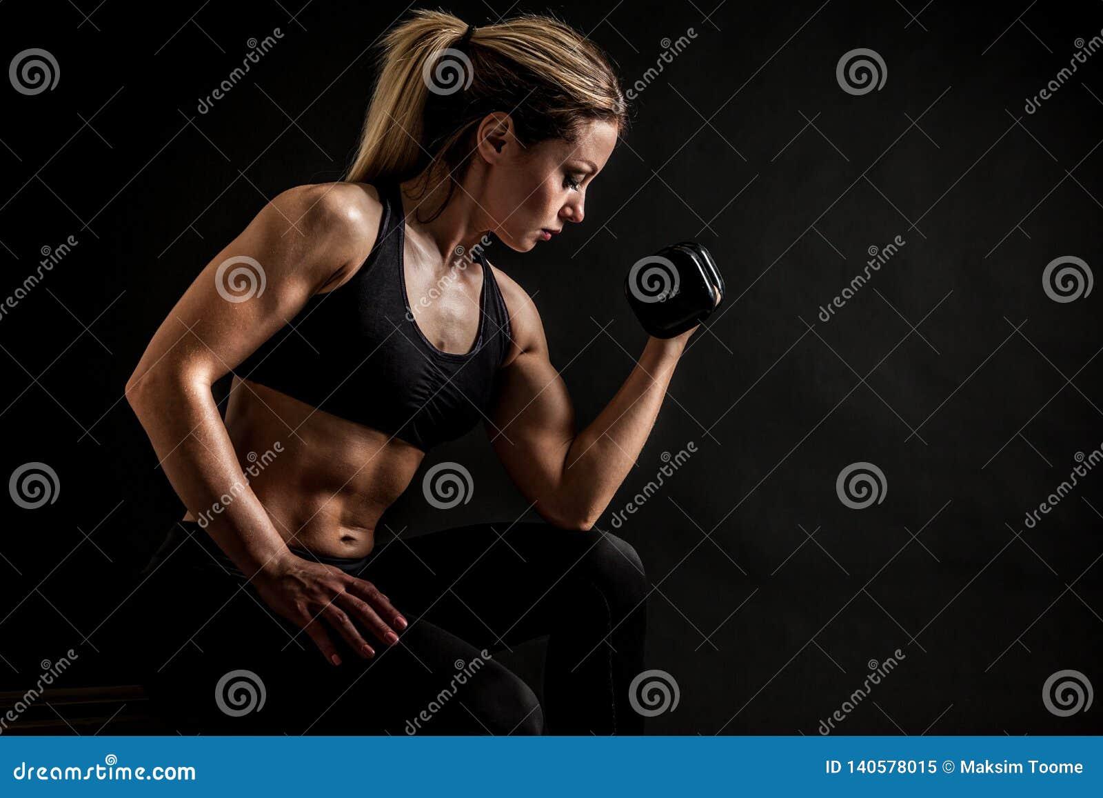 Atletische vrouw die omhoog spieren met domoren pompen